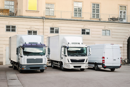Different small and medium courier service  trucks and van at building courtyard. City delivery cargo shipping company vehilcles parked at street. Archivio Fotografico
