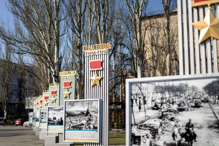Kiev, Ukraine - April 3rd, 2019: Memorial alley with monument with soviet hero star medals to hero-cities of Great Fatherland War or ww2 and historical photos exhibition