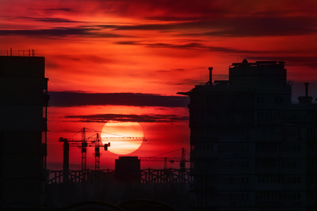 Citysacpe silhouette of buildings and construction site cranes with big bloody fiery red sun at dusk on background. Scenic industrial landscape.