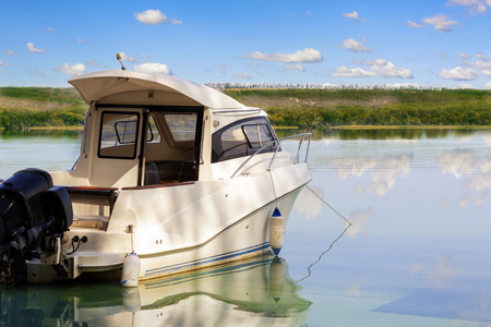 Big luxury fishing boat with cabin moored near river or lake shore in still water. Blue sky on the background. Summer adventure, relax and travel. Boat rental service.