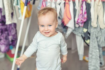 Cute adorable caucasian toodler boy laughing and hving fun playing home with mess and clothes dryer on background. portrait of Funny playful baby at nursery room. Happy and carefree childhood concept.