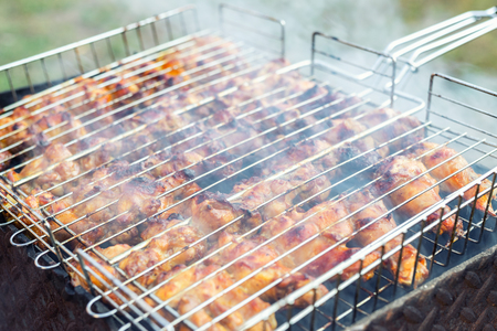 Close-up chicken wings cooking in metal barbecue grid on grill brazier. Outdoors weekend party on backyard. Tasty golden brown delicious bbq meal.