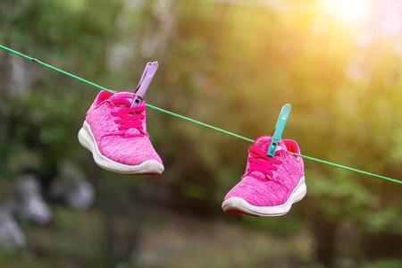 Pair of bright sport fitness sneakers hanged on clothespin at backyard after laundry outdoors. Preparartion for running training or marathon.