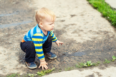 Cute little caucasian blond toddler boy having fun lying in a puddle after rain outdoors. Curious child discovering world in mud