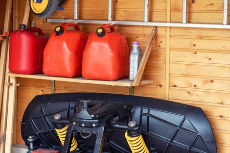 Garage corner with three red plastic fuel cans , staircase and snow plough for atv with wooden wall on background. Petrol gas containers reserves storage at vehicle home garage