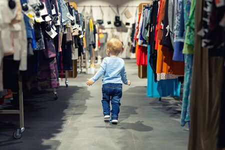 Cute caucasian blond toddler boy walking alone at clothes retail store between rack with hangers. Baby discovers adult shopping world. Baby get lost at big hypermarket shopping mall. Stock Photo