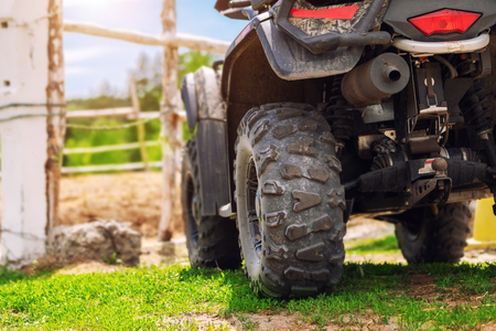ATV quad bike vehicle standing near wooden fence at farm or horse stable. Back view of all wheel drive motorcycle at farm. Rural countryside machine.