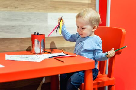 Cute little caucasian blond toddler boy sitting at table and drawing at children area at retail clothes store. Baby spending time at kid's zone during parents shopping in mall. Retailer child care . Stock Photo