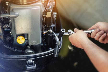 mecánico que repara el motor de la lancha inflable en el garaje del barco. Servicio y mantenimiento estacional de motores de barcos. Motor de embarcación con tapa abierta.