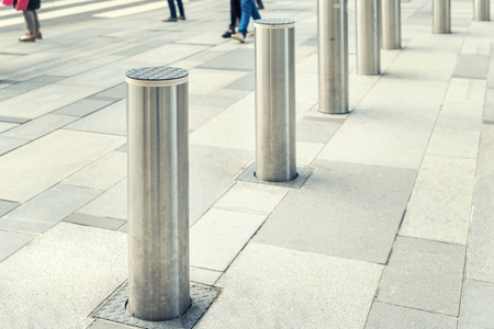 Stainless steel bollard entering pedestrian area on Vienna city street. Car and vehicle traffic access control.