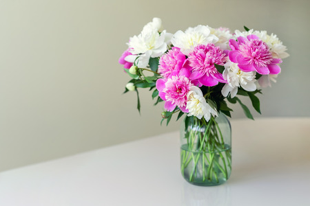 Bouquet of fresh big pink, white and cream peonies in simple glass jar on glance table indoor. Vase with beautiful tender spring flowers on glass table. 写真素材