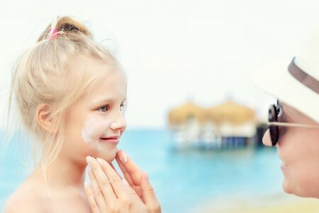 Mother applying sunscreen protection creme on cute little toddler boy face. Mom using sunblocking lotion to protect baby from sun during summer sea vacation. Children healthcare at travel time.