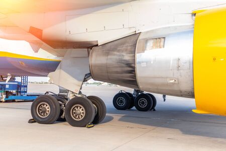 Close-up big commercial plane engine and landing gear standing on airfiled after aircraft arrival on bright sunny day Stock Photo