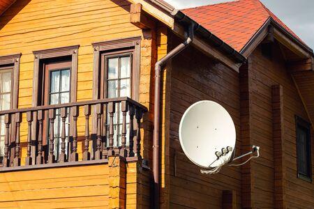 Antenne satellite parabolique blanche accrochée au mur d'une villa de maison de campagne en bois moderne. Récepteur de télédiffusion sans fil.