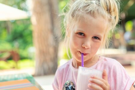 Adorable cute preschooler caucasian blond girl portrait sipping fresh tasty strawberry milkshake coctail at cafe outdoors. Children healthy diet and nutrtion concept.