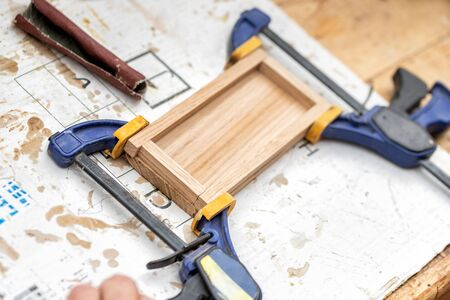 Senior carpenter glueing wooden craft surface and joining with clamps. Woodwork carpenter with equipment and tools at workshop. Handmade diy furniture.Wood part glue joiner.