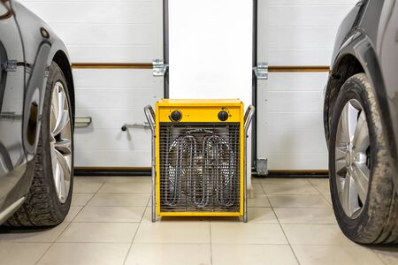 Big heavy industrial electric fan heater in double car garage interior. Two vehicles parked for winter storage in dry warm heating parking for cold winter season. Foto de archivo - 129207895