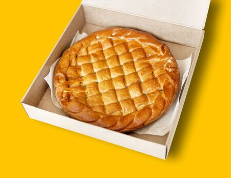 Traditional homemade rustic baked pie with seasonal fruit or meat filling in cardboard box isolated on white. Fast food to go. Bakery delivery menu. Flat lay. Copyspace.