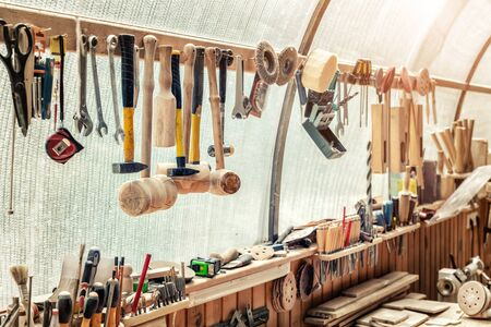Woodwork workshop workbench with many different tools and equipment. Carpentry craftsman work bemch. DIY handmade furniture industry Foto de archivo - 129294366