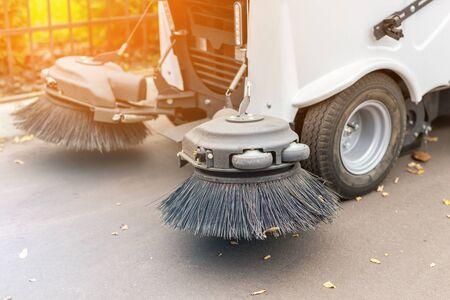 Kleine Kehrmaschine, die nach der Reinigung der Stadtparkgasse auf dem Parkplatz steht. Kehrsaugfahrzeug, das im Herbst Staub und abgefallene Blätter entfernt. Standard-Bild