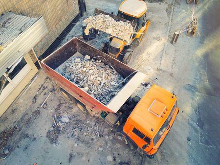 Caricatore bulldozer che carica rifiuti e detriti in un autocarro con cassone ribaltabile in cantiere. servizio di demolizione edile e smaltimento rifiuti edili. Sfondo industriale drone aereo.