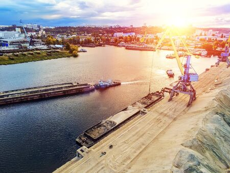 Aerial view of heavy crane loading bulk goods at Dnieper river cargo port terminal in Kiev at evening sunset time. tugboat pushes barge with sand after loading. Industrial inland navigation.