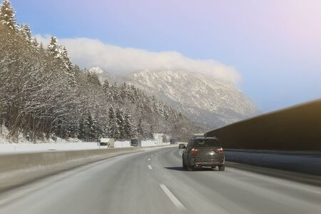 Car running on curve of empty winter highway road with beautiful mountains covered with snow on background. Winter travelling and vacation.