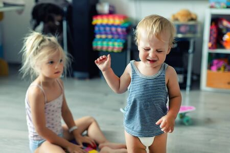 Two little siblings children quarrelling after playing at room at house. Crying offended toddler boy arguing with elder sister. Family rivalry and generation conflict concept. Stock Photo