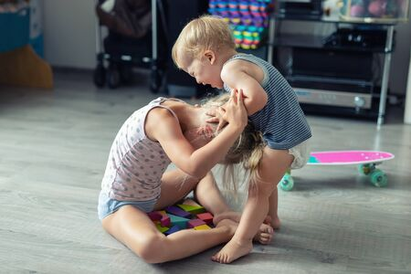 Two little siblings children quarrelling after playing at room at house. Crying offended toddler boy arguing with elder sister. Family rivalry and generation conflict concept.