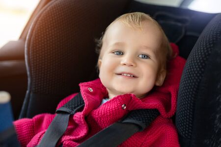 Cute caucasian toodler boy sitting in child safety seat in car during road trip. Adorable baby smiling and enjoying trip in comfortable place in vehicle. Children care and safety on road.