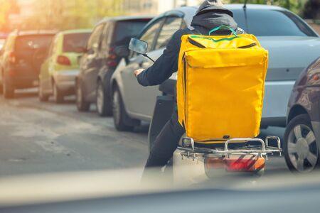 Lebensmittellieferkurier mit großem gelbem Rucksack, der Roller auf Stadtstraße mit Verkehr fährt. Schnelles Mittagessen zum Mitnehmen. Teenager-Job.