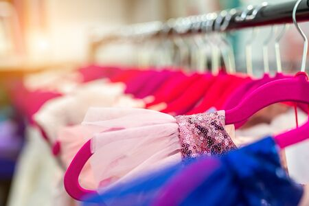 Rack with many beautiful holiday dresses for girls on hangers at children fashion showroom indoor. Kid girl dress hire or sewing studio for celebration birthday party or photography session event. Stock Photo