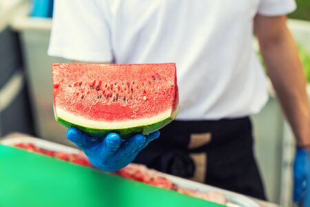 Cook in rubber gloves holding in hand and offering big piece of fresh tasty juicy sliced watermelon for hotel guests at tropical resort outdoors.