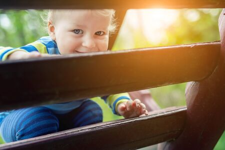 Portrait of cute mischievous caucasian blond baby boy holding wooden banister climbing staircase at outdoor backyard playground. Adorable happy child having fun playing outdoors at park area.