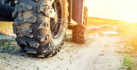 Close-up tail view of ATV quad bike on dirt country road at evening sunset time. Dirty wheel of AWD all-terrain vehicle. Travel and adventure concept.Copyspace.Toned 版權商用圖片
