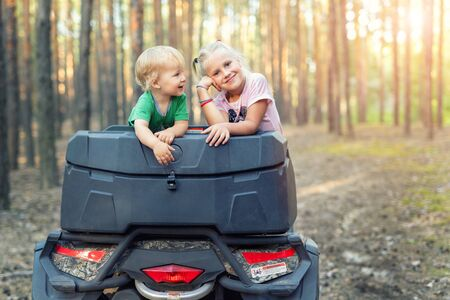 Cute adorable caucasian blond siblings having fun during atv 4x4 off-road adventure trip amog coniferous pine forest on brigh sunny day. Little boy and girl enjoy outdoor sport travel activities