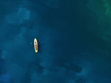 Aerial drone view of family having fun swimming on SUP stand up paddle inflatable surf board. Mother with children enjoy sitting on surfboard at clear blue ocean or sea water during vacation