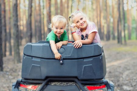Cute adorable caucasian blond siblings having fun during atv 4x4 off-road adventure trip amog coniferous pine forest on brigh sunny day. Little boy and girl enjoy outdoor sport travel activities. Reklamní fotografie