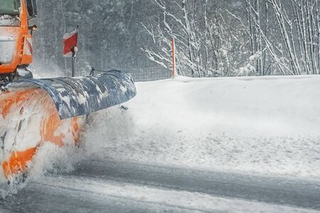 Snowplow truck removing dirty snow from city street or highway after heavy snowfalls. Traffic road situation. Weather forecast for drivers. Seasonal road maintenance. Stockfoto
