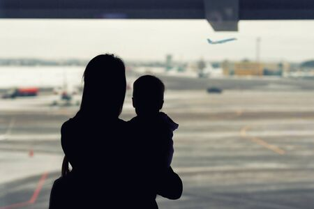 Silhouette of mother holding on hands little toddler boy with window of airport on background. Departure and arrival. Single mother with child emigration. Mom with son meeting or seeing off father. Stock Photo