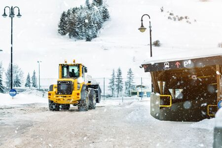Big loader machine with steel metal chains removing big snow pile from city street at alpine mountain region in winter. Heavy snowfall aftermath. precipitation cleaning equipment. 写真素材