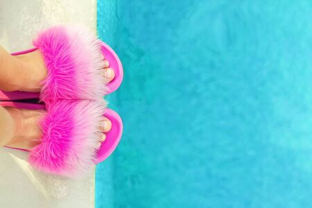 Girl or woman feet in glamour fashion fluffy slippers standing on edge of pool with clear blue water. Legs wearing flip-flops sliders near poolside. Vacation beggining concept. Copyspace.