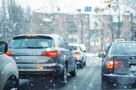 Many cars standing in row on traffic lights during snowfall in cold winter morning. Traffic jam on city street at snowstorm weather. Stockfoto
