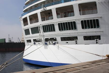 Close-up tail view of big modern white cruise ship liner morred with mooring cable at cargo port of sea or ocean.