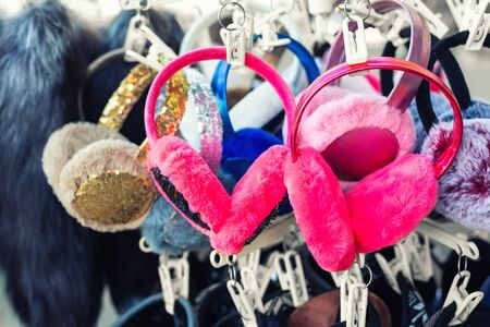 Lot of many multicolored bright fluffy fur earphones hanged on rack at store display for sale. Cute warm cold season clothes accessories.