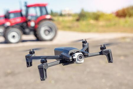 Compact black drone quadcopter with surveillance camera flying low against red agricultural tractor machines. Usage modern technologies and agriculture equipment machinery for farming and agronomy. Foto de archivo