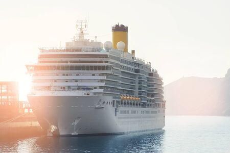 Big modern white cruise ship liner morred with mooring cable port of sea or ocean at beautiful morning sunrise time. Travel and vacation. Adventure journey beginning concept.