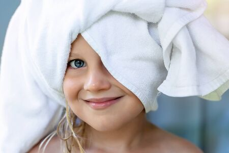 Cute adorable caucasian little blond girl wearing white towel on we head after shower or bathing at bathroom. Portrait of cheerful smiling female child.