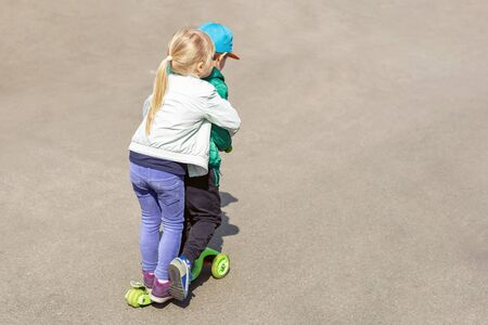 Two frineds boy and girl having fun riding one scooter together simultaneously. Children siblings, brother and sister enjoying outdoor sport activities.