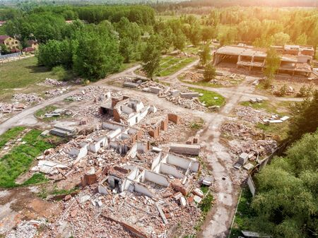 Aerial drone view of old demolished industrial building. Pile of concrete and brick rubbish, debris, rubble and waste of destruction ruins of abandoned actory or plant. Earthquake city landscape.